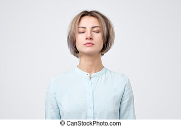 Young european woman in blue shirt closing eyes. No emotion on her face.