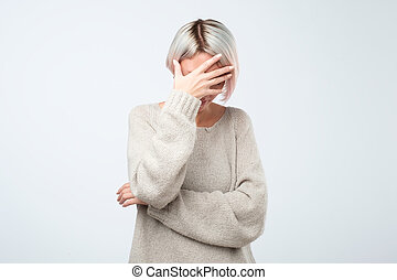 Young european woman in gray sweater hides her face, studio photo isolated on gray background.