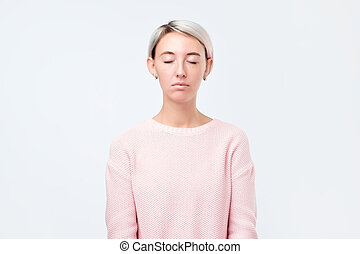 Young european woman in pink sweater closing eyes.