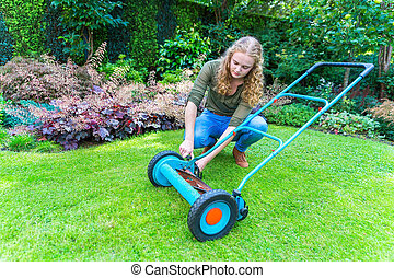 Young european woman reparing lawn mower in garden