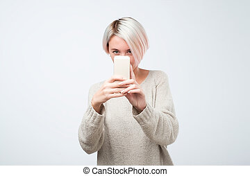 Young european woman with short dyed hair is taking photo on a smartphone
