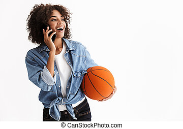 Young excited sports woman african holding basketball posing isolated over white wall background talking by mobile phone.