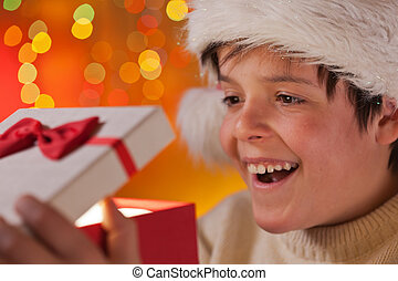 Young excited teenager boy opening his christmas present