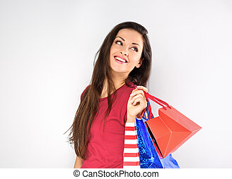 Young excited toothy smiling woman with shopping bags looking on empty copy space