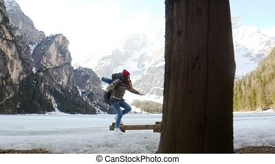 Young excited woman traveling on a lago di braies coast with...