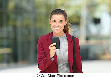 Young executive holding a phone and looking at you
