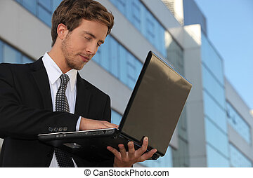 Young executive using a laptop outside an office building