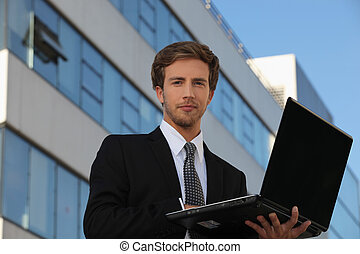 Young executive using his laptop outside an office building