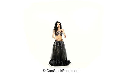 Young exotic belly dancer with long dark hair shaking her hips, on white, slow motion