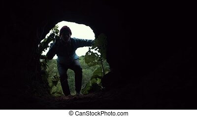 Young explorer looks into dark cave chamber with flashlight in his hand