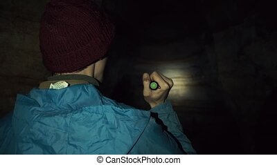 Young explorer walking in cave with hand flashlight. Deep...