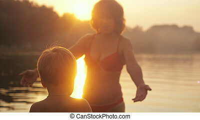 Young family a little child having enjoyable time with his grandma at the sea during beautiful sunset happy vacation time.