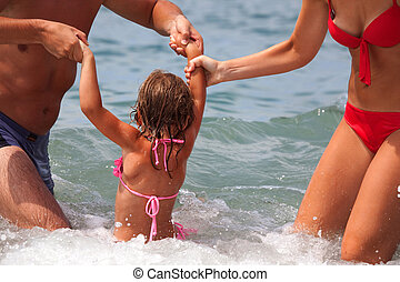 young family bathes in sea. wet happy daddy and mum play with daughter standing in water. Parents hold child for hands