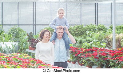 Young family choosing flowers in the greenhouse. - Watching...
