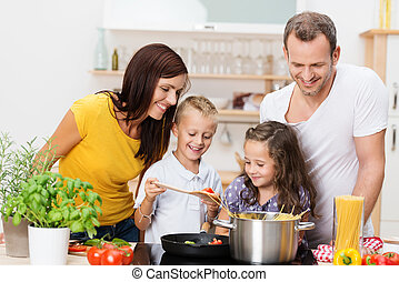 Happy young family with Mum, Dad and two young children cooking in the kitchen preparing a spaghetti meal together