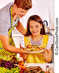 Young family cooking pizza at kitchen.