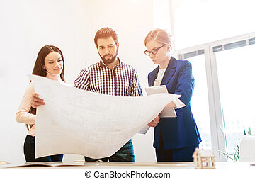 Young family couple purchase rent property real estate . Agent giving consultation to man and woman. Signing contract for buying house or flat Keeps the plan of the house or apartment in the hands.