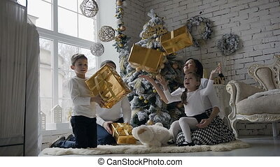 Young family dressed in white clothes, sit on the floor near the Christmas tree in the living room with a large window and rejoice in the gifts that are in golden boxes