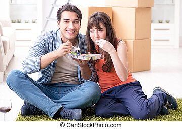 Young family eating food in new apartment after moving in