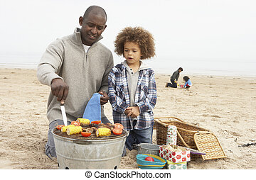 Young Family Enjoying Barbeque On Beach