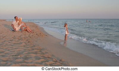 Young family enjoying summer vacation in evening on sand beach