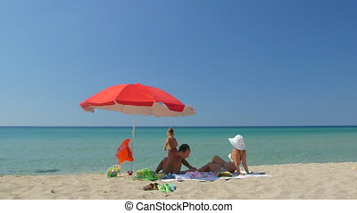 Young family enjoying summer vacation on sandy beach beside turquoise sea