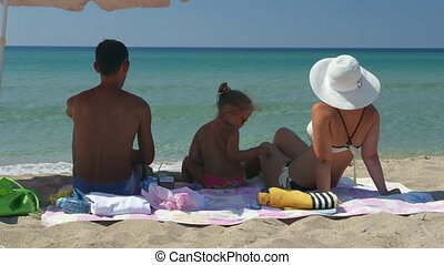Young family enjoying summer vacation on sandy beach near turquoise sea water