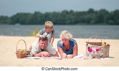Young family enjoying weekend on river bank