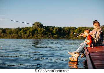 Young family fishing on the pier on the river or lake in ...