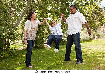Young Family Having Fun in the Park - Hispanic Man, Woman...