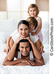 Young family having fun on the bed