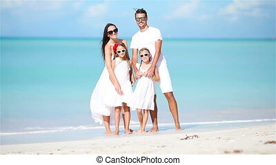 Young family having fun on white tropical caribbean beach