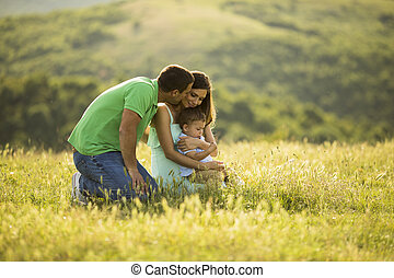 Young family having fun outdoors in the field