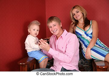 young family in armchair in red room