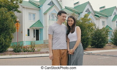 Young family in front of new house