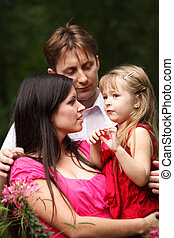 Young family in summer garden. Mum holds daughter on hands. Man embraces them.