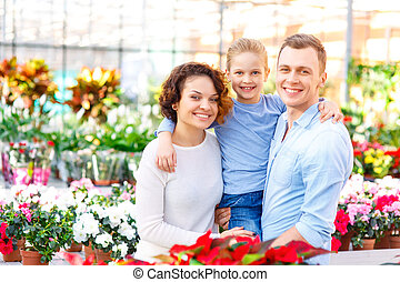 Young family in the greenhouse. - Greenhouse shopping. Happy...