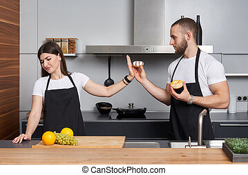 Young family in the kitchen. Man offering his girl donuts, but she is refusing