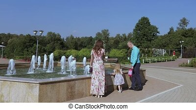 Young family in the park with a fountain