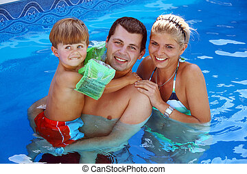 Young family in the pool - Young family with one child in ...