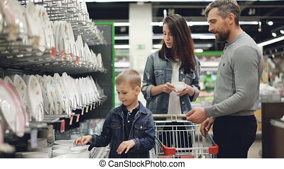 Young family is choosing bowls in supermarket in kitchenware...