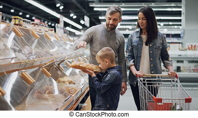 Young family is choosing bread in bakery department in supermarket, little boy is taking loaf from plastic container and smelling it then putting in trolley.