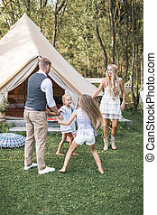 Young family is playing together on a sunny day in park. Father, mother and two daughters in casual boho clothes dancing and jumping, holding hands in front of big white tipi wigwam tent