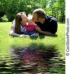 Young Family kissing baby by Water