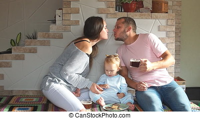 Young family kissing in the kitchen