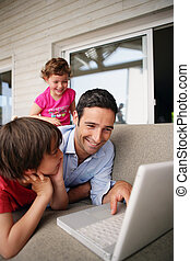 Young family laughing at a laptop