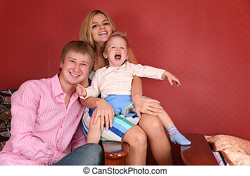 young family laughing in armchair in red room