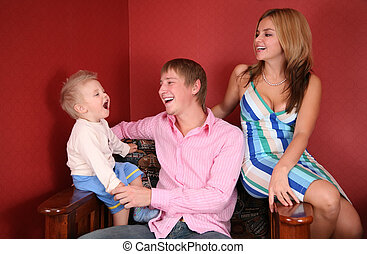 young family laughing in red room