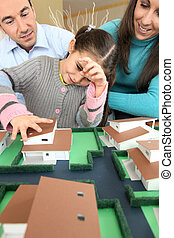 Young family looking at model house