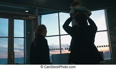 Young family looking out airport window at sunset